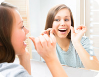 Beauty young woman flossing her teeth at home. Pretty teenage gi